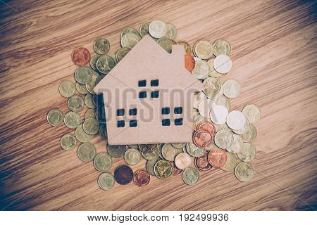 real estate investment wood house model with coin savings plans for housing financial concept dark tone