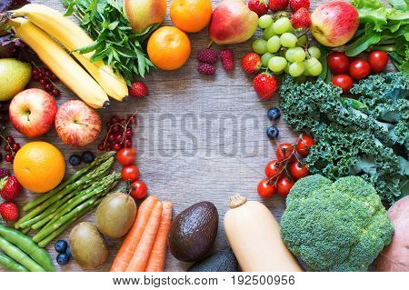 Top view of apples, bananas, berries, oranges, carrots, tomatoes, broccoli, beans, butternut squash, avocado, and asparagus, on the grey wooden table, top view, copy space for text, selective focus