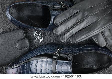 Classic men's shoes cufflinks gloves and purse on the black leather. View from above