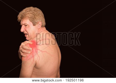 Close-up of senior shirtless man with shoulder pain over white background