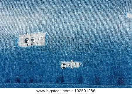 Luxurious stylish background of torn jeans inlaid with rhinestones. Texture. View from above