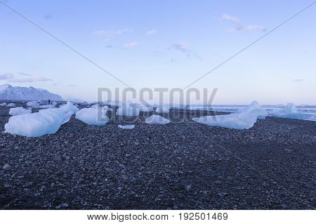 Ice breaking on black sand rock sand beach natural winter skyline background Iceland