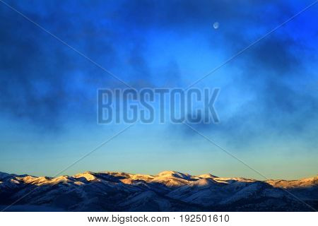 Mountain range in winter sunlight on snow capped peaks with moon