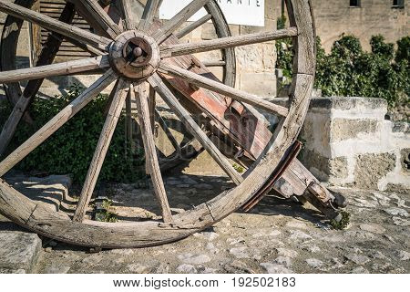 Vintage wood bullock wheel with sun shine summer Matera Italy.