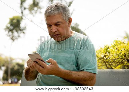 Senior man typing message in the park