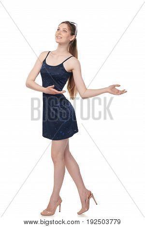 Full length of smiling leggy young female in blue mini dress and sunglasses on head welcoming or showing blank copy space, isolated on white background