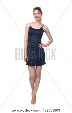 Full length of smiling leggy young female in blue mini dress and sunglasses on head, isolated on white background