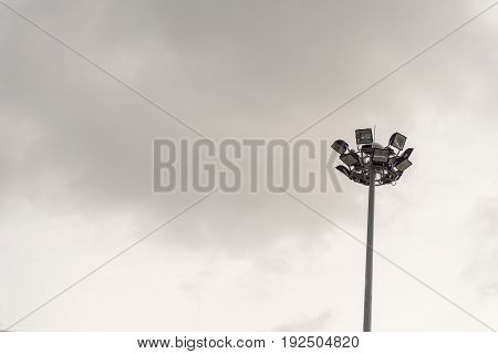 Stadium lights tower on cloudy sky background