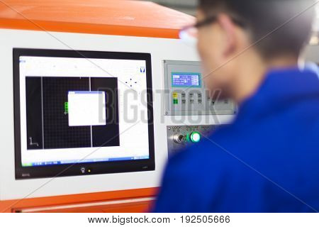 young mechanic technician making drawings by computer in intelligence manufacturing factory