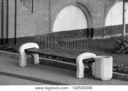 Modern wooden bench and recycle bin in the autumn city park
