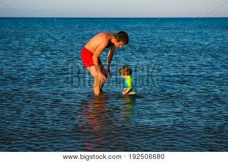 Father And Daughter Playing Together In The Sea Water