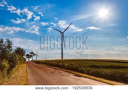 A road and wind turbines under blue sky.