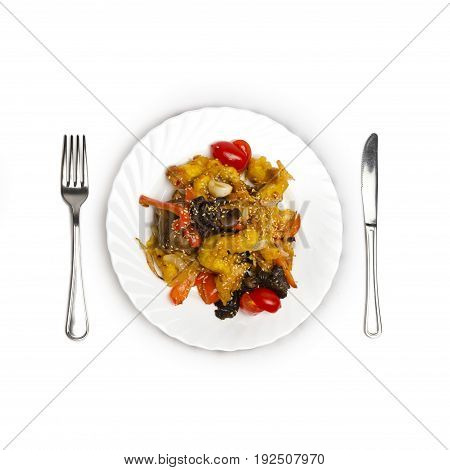 Chicken in sweet and sour sauce, chicken fillet is fried together with vegetables and wood mushrooms on the white plate isolated