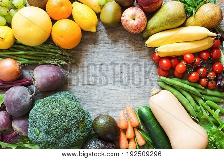 Different fruits vegetables, broccoli, carrots, avocado, tomatoes, beetroot, bananas, apples, pears, lemons, greens on the grey table selective focus