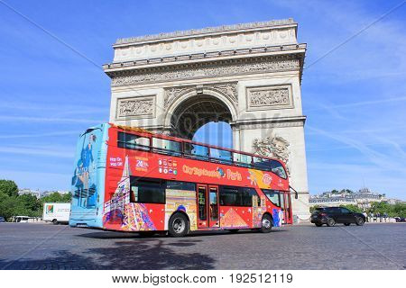PARIS, FRANCE - JUNE 5, 2017: Hop on Hop off red tourist tour bus in front of Arc de Triomphe. Popular travel landmark in the city of Paris, most visited city in Europe.