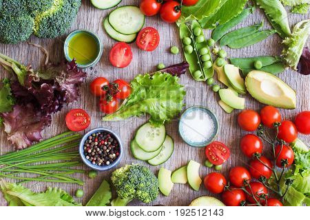 Cut ingredients for salad, fresh tomatoes, cucumber, avocado, lettuce, spring onion, broccoli on the grey wooden table, top view selective focus