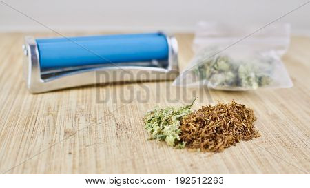Blue rolling machine bag with weed and marijuana on wooden desk.