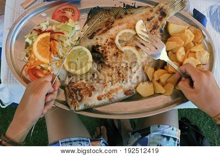 Eating a grilled turbot on the beach