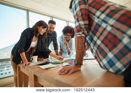 Team of creative professionals working together in office. Group of young man and woman working on new business project in office.