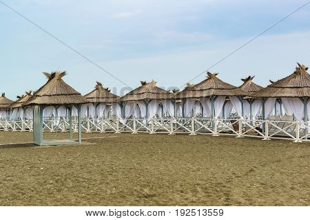 Equipped with tents with thatched roofs and white curtains deserted beach on a cloudy day