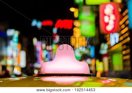Close-up bright pink light box on the roof of yellow taxi cab parking at entertainment or shopping area at night time for serving shoppers or general passengers