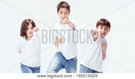 Group of smiling kids wearing jeans and white shirts.