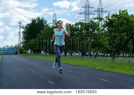 The girl is running around the stadium. Training outdoors. From the side view.