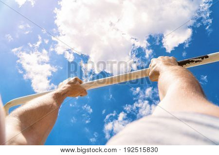First-person view of the horizontal bar. The guy pulls up on the bar. Workout outdoors. Blue sky on blackground.