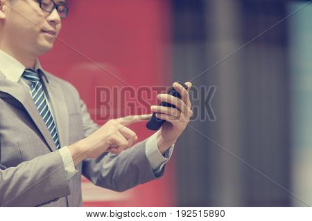Asian business man hand using smart phone in subway station, train passing by at the background.