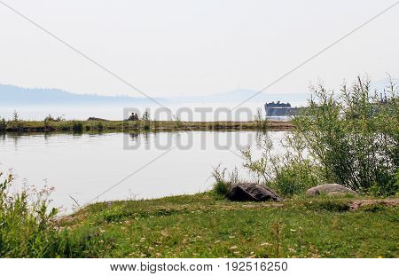 Landscape with a hugging loving couple on the bank of a misty river