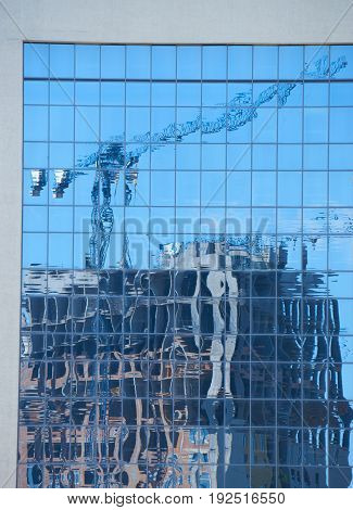 reflection of the modern apartment building under construction in the office building windows