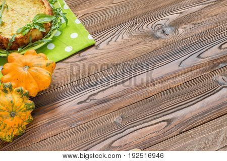 squash casserole decorated by basil leaf and arugula on light green plate at wooden table with squash fruits
