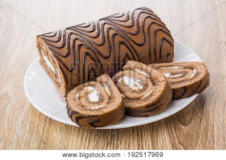 Pieces Of Swiss Roll In White Plate On Table