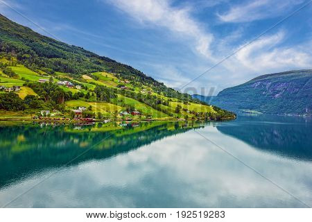 rural lake landscape Norway, Olden green hills seaside. fjord in summer.