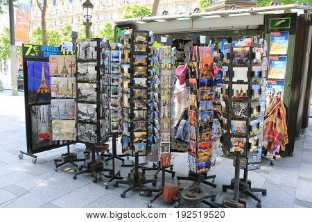 PARIS, FRANCE - JUNE 5, 2017: Souvenir kiosk and shop at Avenue des Champs Elysees. Selling variety of gifts, postcards, magnets, posters, keychains, tourist maps and souvenirs.