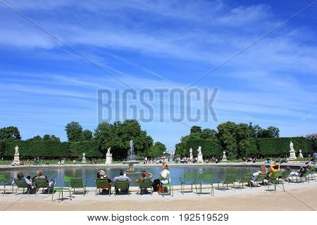 People relaxing in Tuileries Palace open air park with the view to Champs Elysees and Arc de Triomphe in the background in Paris, France. Summer day scene with empty clear sky