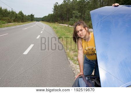 Beautiful Woman Leaning Over Looking Into The Engine Compartment Of A Broken Down Car