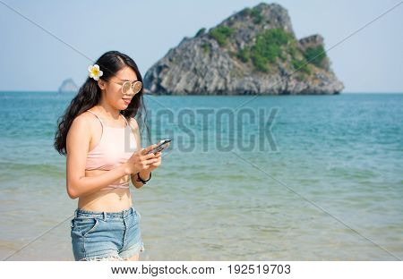 Girl Looking At The Phone While Walking On The Beach