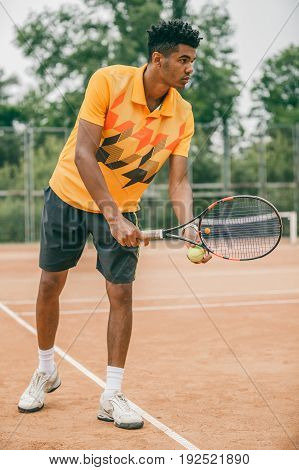 Young tennis player with racket ready to serve a tennis ball. Professional tennis player starting set.