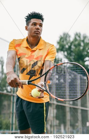 Low angle view of determined young black man playing tennis. Tennis player posing in front of a tennis court