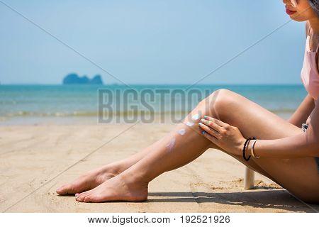 Girl Using Sun Lotion On The Beach