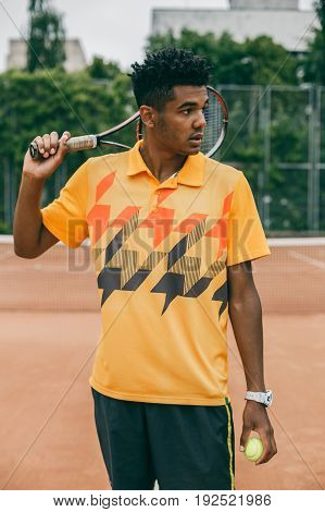 Portrait of a confident tennis player standing on tennis court. Handsome young man in polo shirt holding tennis racket