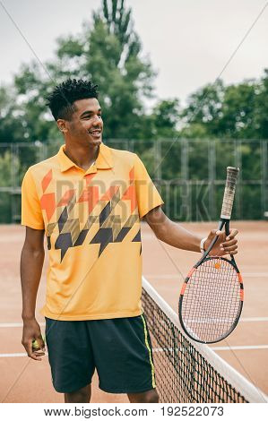 Portrait of a smiling tennis player with racket on tennis court. Young black man playing tennis in orange polo shirt.