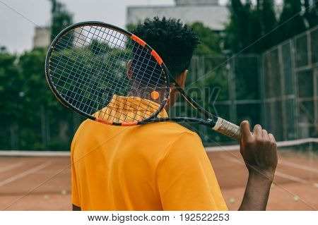 Back view portrait of a man playing in tennis outdoors. Young african man holds a tennis racket on his shoulder.