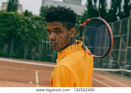 Young african man holds a tennis racket on his shoulder. Portrait of young african man playing tennis.