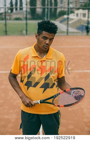 Ready to play. Handsome young man in sports clothing carrying tennis racket and looking at camera on the court.