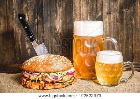 Horizontal studio shot of hamburger and two glasses of beer at wooden wall.