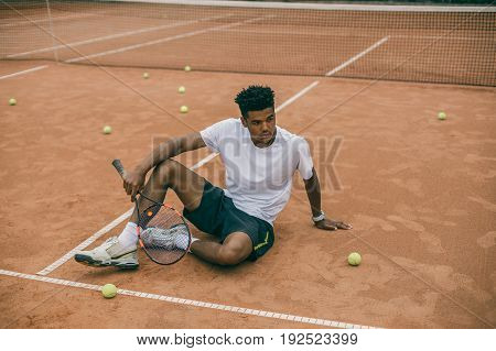 African man resting and chilling on the break time. Young man in sports uniform sits on the ground of a tennis court.