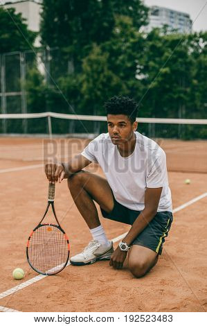 Young man hanging out in the tennis courts sitting on ground. African man resting and chilling on the break time.
