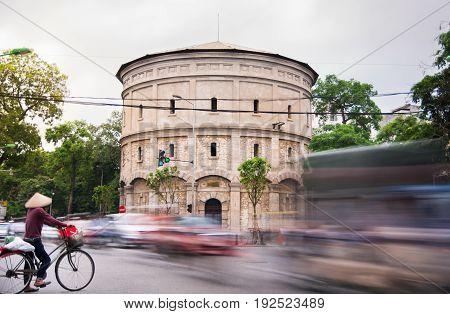 Hanoi, Vietnam - May 24, 2017: Hanoi Water Tower Building With Busy Traffic Scene Of Many Motorbikes